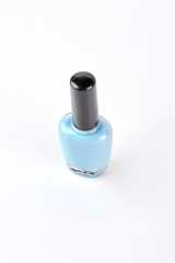 Bottle with light blue nail polish. Pastel color nail varnish isolated on white background.