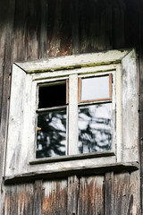 Window and wall of the old abandoned wooden house. Details of vintage wall and window frames.