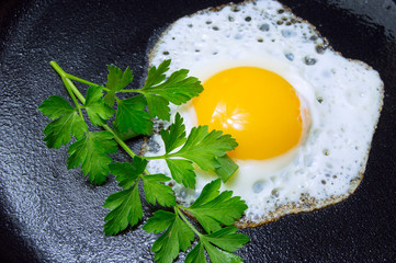 Fried egg with parsley on pan for breakfast close up