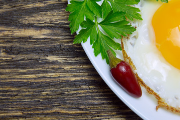 Fried egg with green parsley on plate with pepper close up, on vintage wooden background