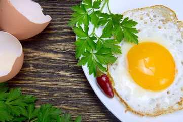 Fried egg with green parsley on plate with pepper and eggshell close up, on vintage wooden background