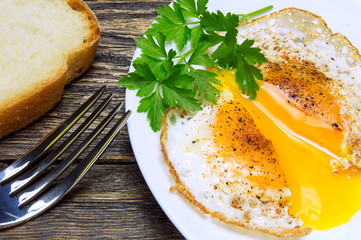 Sliced fried egg with spices, green parsley, pepper, bread and fork on plate, vintage wooden background