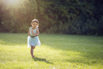 Little girl running in park with no shoes on grass