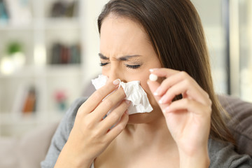 Woman coughing covering mouth with a tissue at home