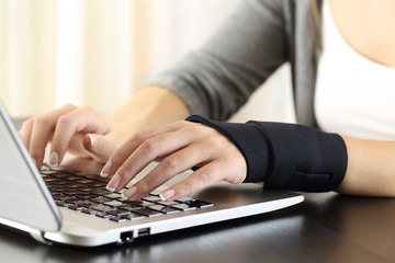 Woman hands with injured wrist working on line