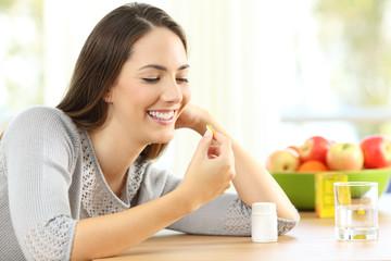 Woman taking omega 3 vitamin pills