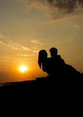 silhouette of couple on beach at sunset