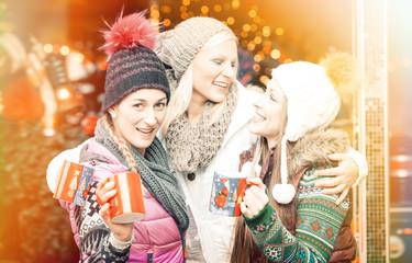 Frauen trinken Glühwein Becher auf deutschen Weihnachtsmarkt