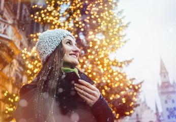 Frau schaut sich den Weihnachten Schmuck der Stadt an während es schneit