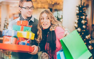 Paar - Mann und Frau - mit Geschenken zu Weihnachten und Einkaufstüten in einer Mall vor einem Weihnachtsbaum