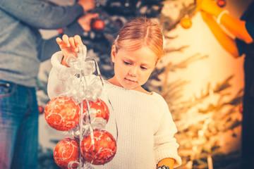 Kind schmückt den Weihnachtsbaum