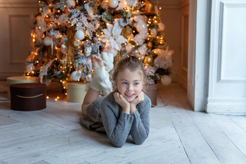 Young girl lies near a Christmas tree