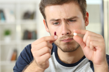 Man wondering about pill or capsule