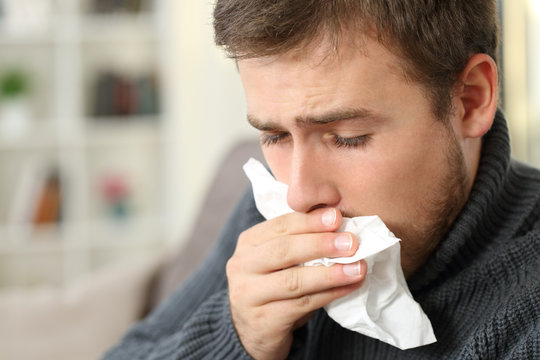 Man coughing covering mouth with a tissue at home