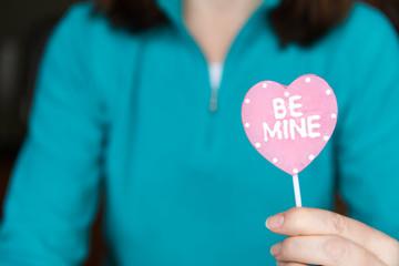 Woman holding a candy heart sucker