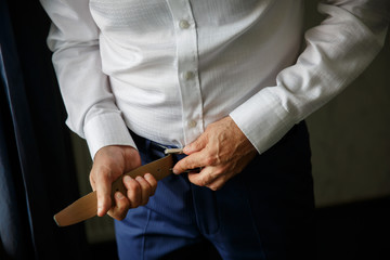 Man. People, business,fashion and clothing concept - close up of man in shirt dressing up and adjusting belt