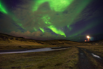 Northern lights Aurora Borealis above landscape with light tower