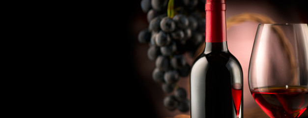 Wall Murals Wine Wine. Bottle and glass of red wine with ripe grapes over black background