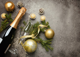 A bottle of champagne with various chocolate candies of a round shape an empty glass and spruce branches lie on a gray background under the concrete. Celebratory concept.