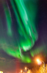 Northern lights Aurora Borealis above street in Iceland