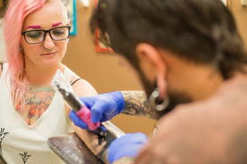 A bearded tattoo artist , in a brown t-shirt fills the arm a tattoo of the girl with pink hair