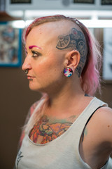 A young girl with a shaved head, pink hair and a tattoo on his head and chest. Many piercings on the face and body. Tunnels in the ears.