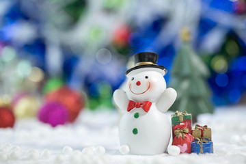 Snowman Standing with Gift Box on bokeh background. Christman Concept.