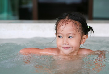 Happy little Asian girl lying in the hot tub.