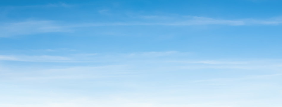 An aerial background view from of clear blue skies and white faint clouds - panoramic web banner