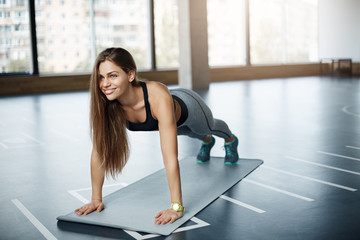 Beautiful sporty female doing push ups smiling alone in the morning gym. Striving for a perfect body.