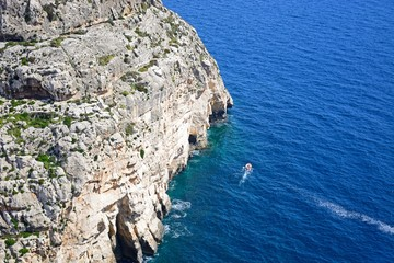 View looking down at Blue Grotto Cove with tourists in a tour boat, Blue Grotto, Malta.