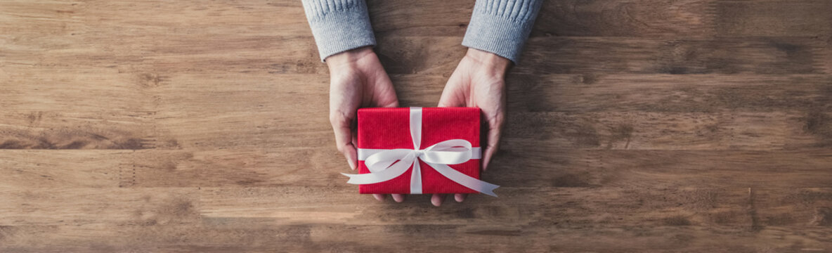 Woman giving a christmas or birthday gift - web banner