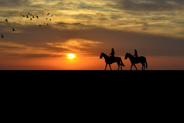 A couple on a horse riders at sunset