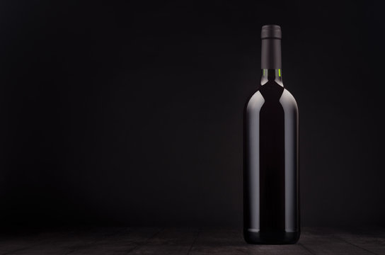Bottle of red wine mock up on elegant dark black wooden background, copy space. Template for portfolio, advertising, design, branding identity, cover magazine, bar and restaurant menu.