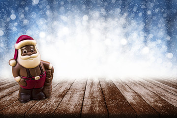 Christmas background with bokeh effects and chocolate Santa Claus