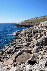 View along the rugged coastline with rock salt pools in the foreground, Blue Grotto, Malta.