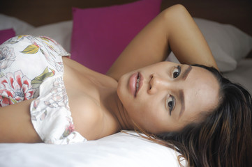 young attractive and beautiful Asian woman lying on bed at bedroom posing sexy in beauty indoors studio set