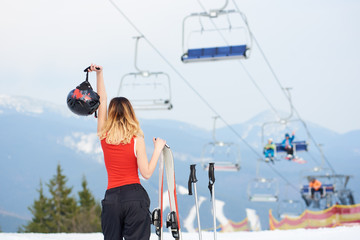 Back view of young female skier standing on the top of the snowy hill with ski equipment at winter ski resort. Ski-lift and mountains on the background. Ski season and winter sports concept copyspace