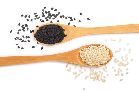 Black and white sesame seeds in a wooden spoon isolated on white background top view