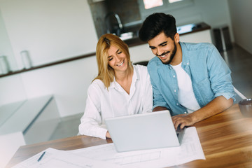 Handsome young man and attractive woman working on laptop