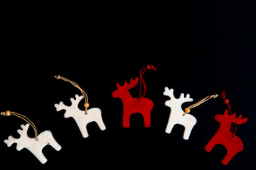 Red and white felt rein deers isolated on black