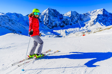Wall Mural - Girl on skiing on snow on a sunny day in the mountains. Ski in winter seasonon, the tops of snowy mountains in sunny day. South Tirol, Solda in Italy.