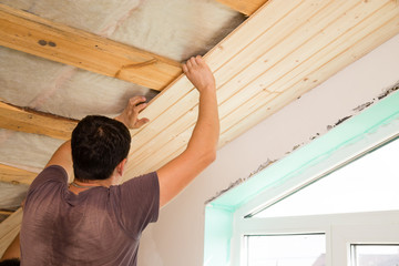 worker working on a wooden ceiling in the house
