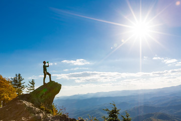 Man with a water bottle at the edge of a cliff overlooking the mountains below