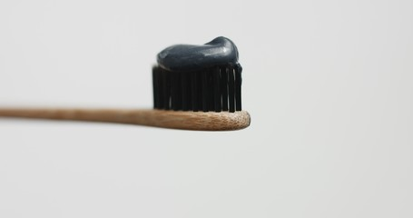 Black toothpaste on toothbrush with black bristles and wooden handle isolated