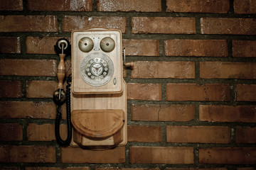 Urban background of a brick wall with an old out of service payphone