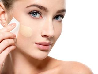 Girl applies  tonal foundation  on the face use sponge