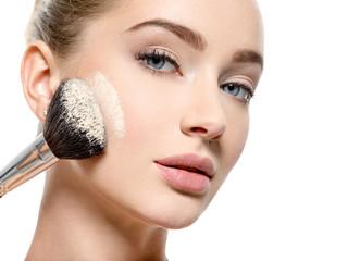 Girl applies  powder  on the face using makeup brush.
