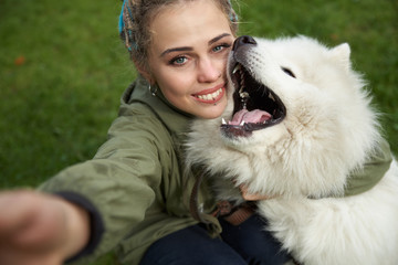 selfie of a young woman in green coat and multicolored dreadlocks with his white Samoyed dog in the autumn Park