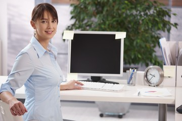 Portrait of happy young woman working at office